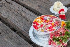 Riegue en el cuenco mezclado con perfume y flores Imagen de archivo
