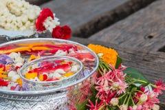 Riegue en el cuenco mezclado con perfume y flores Fotografía de archivo