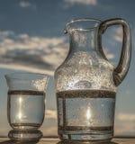 Riegue en un vidrio y en una jarra Fotografía de archivo