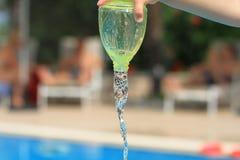 Riegue fluir de la botella sostenida a mano de niño Imagen de archivo