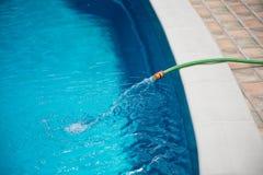 Riegue fluir de la manguera en la piscina, relleno, manteniendo imagenes de archivo