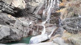 Riegue la conexión en cascada sobre rocas, la cascada y colores del otoño en los árboles de las montañas, amarillos y rojos metrajes