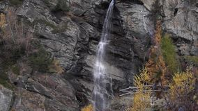Riegue la conexión en cascada sobre rocas, la cascada y colores del otoño en los árboles de las montañas, amarillos y rojos almacen de metraje de vídeo