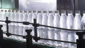 Riegue la línea de embotellamiento para procesar y embotellar el agua de manatial pura almacen de metraje de vídeo