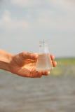 Riegue la mano de la prueba de la pureza que sostiene el frasco químico con el líquido, el lago o el río en el fondo fotografía de archivo