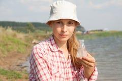 Riegue a la mujer de la prueba de la pureza que sostiene el frasco químico con agua, el lago o el río en el fondo imágenes de archivo libres de regalías