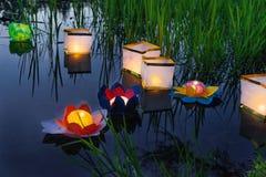 Riegue las linternas amarillas ardientes en el lago en medio de la hierba alta Foto de archivo