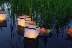 Riegue las linternas amarillas ardientes en el lago en medio de la hierba alta Fotos de archivo