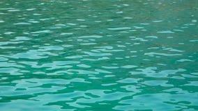 Riegue las ondulaciones en la superficie del agua azul metrajes