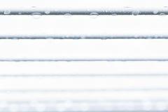Riegue los descensos en un alambre con un fondo blanco Fotos de archivo libres de regalías