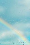 Riegue los descensos en una ventana con el arco iris en el fondo Fotografía de archivo