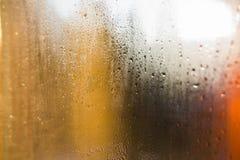 Riegue los descensos sobre el vidrio amarillo, gotitas de la lluvia en el fondo de cristal Fotos de archivo
