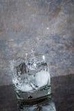 Riegue salpicar del vidrio en una superficie mojada Imágenes de archivo libres de regalías
