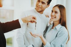 Rieltor Is Giving A House Key To Young Couple. Bright Office. Keys In A Hand. Buying A Property. Panoramic Windows. Business Meeting. Customer And Buyer. Offer stock photography
