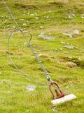 Riemen und Schrott im grünen Yard, Eisen verdrehten das Seil, das durch Schraubenkarabinerhaken und -gummimuffen am Anker im Bode lizenzfreie stockfotos