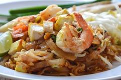 Riempia la tagliatella di riso fritto tailandese di scalpore con gamberetto e l'uovo sul piatto fotografia stock