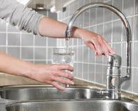 Riempimento del vetro di acqua Fotografie Stock Libere da Diritti