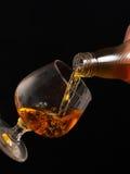 Riempimento del vetro di brandy su un fondo nero Immagine Stock