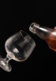 Riempimento del vetro di brandy su un fondo nero Immagini Stock
