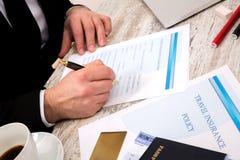 Riempimento della forma di reclamo di assicurazione di viaggio Immagine Stock