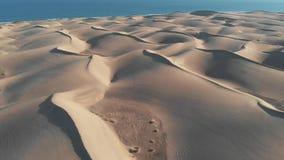 a?rien Vol cinématographique au-dessus du désert au coucher du soleil - les dessus des dunes de sable ont moulé des ombres Panora banque de vidéos