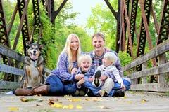 Riendo, familia feliz que se sienta en el puente en Autumn Forest fotos de archivo