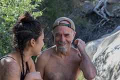 Riendo, sonriendo, padre maduro mayor con la hija hispánica afuera en la naturaleza que se divierte junto foto de archivo libre de regalías