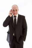 Riendo, un más viejo hombre de negocios con un teléfono Imagen de archivo libre de regalías