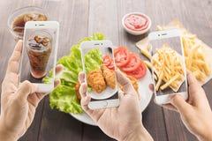 Riends genom att använda smartphones för att ta foto av stekt kyckling och fre royaltyfri bild