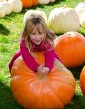 Riesenkürbis und kleines Mädchen Lizenzfreie Stockfotos