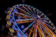 Riesenrad nachts mit einer Bewegungsunschärfe und Blendenflecken Stockfotos