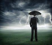 Riesgo y crisis - hombre de negocios debajo de la tormenta imagen de archivo