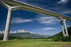 Riesige Brücke und die Alpen Stockfotografie