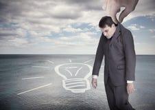 Riesige Hand, die weg von einem Geschäftsmann auf einer Oberfläche fällt Lizenzfreie Stockfotografie