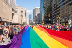 Riesige homosexuelle Regenbogenflagge über der Straße an der Schwulenparade lizenzfreie stockbilder