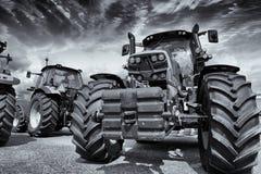 Riesige Landwirtschaftstraktoren und Sturmwolken Stockfotos