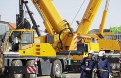 Riesige mobile Kräne und Gebäudearbeitskräfte Stockbild