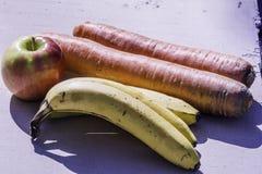 Riesige organische Karotten gegen Organische Banane und ein großer organischer Apfel - nur in Amerika Lizenzfreie Stockfotografie