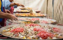 Riesige Paella in der Vorbereitung Addierte Tomaten und Meeresfrüchte Lizenzfreie Stockbilder