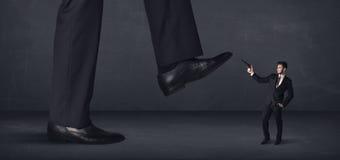 Riesige Person, die auf ein Kleinunternehmerkonzept tritt Lizenzfreies Stockfoto
