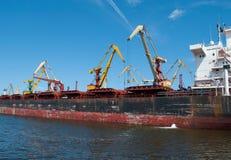 Riesige Portkräne und ein Frachtschiff Lizenzfreies Stockbild