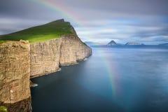 Riesige Seeklippen auf Färöern mit einem Regenbogen Stockbilder