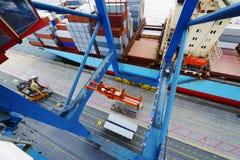 Riesiger Kran, der ein Containerschiff im Hafen belädt Stockbilder