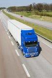 Riesiger Lastwagen, der durch Landschaft beschleunigt Lizenzfreie Stockfotos