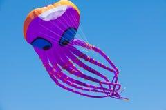 Riesiger purpurroter Krakendrachen, 100 Fuß lang, in der Luft, gegen reinen blauen Himmel Stockfotografie