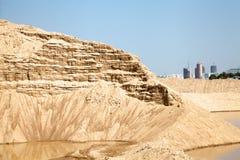 Riesiger Sandhaufen gegen den blauen Himmel Sandextraktionsbergwerk Stockfotos