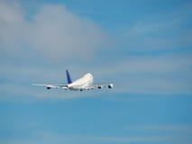 Riesiges Flugzeug entfernt sich in einen blauen Himmel Stockbild