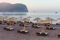 Riet sunshades op het overzeese strand stock afbeeldingen