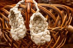 Rieten bastschoenen op een houten mand, Russische amulet Stock Afbeeldingen