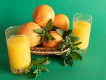 Rieten die kom met sinaasappelen met munt, naast een glas met jus d'orange op een groene achtergrond worden verfraaid royalty-vrije stock fotografie